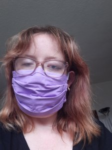 A photo of me with messy lockdown hair, wearing a purple face covering.